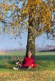 Ανώτερο άτομο με τη συνεδρίαση σκυλιών στη χλόη που κλίνει στο δέντρο Στοκ εικόνες με δικαίωμα ελεύθερης χρήσης