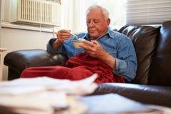 Ανώτερο άτομο με τη φτωχή διατροφή που κρατά το θερμό κατώτερο κάλυμμα Στοκ Φωτογραφία