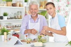 Ανώτερο άτομο με τον εγγονό που προετοιμάζει το γεύμα στην κουζίνα Στοκ Εικόνα