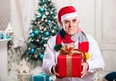 Ανώτερο άτομο με το κιβώτιο δώρων στο υπόβαθρο Χριστουγέννων Στοκ φωτογραφίες με δικαίωμα ελεύθερης χρήσης