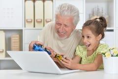 Ανώτερο άτομο με το παίζοντας παιχνίδι στον υπολογιστή εγγονών Στοκ Φωτογραφίες