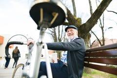 Ανώτερο άτομο με το ποδήλατο στην πόλη, που κάθεται στον πάγκο, που πίνει coff Στοκ εικόνες με δικαίωμα ελεύθερης χρήσης