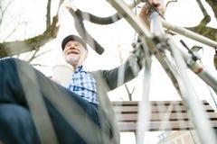 Ανώτερο άτομο με το ποδήλατο στην πόλη, που κάθεται στον πάγκο, που πίνει coff Στοκ Φωτογραφίες