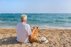 Ανώτερο άτομο με το σκυλί στην παραλία στοκ φωτογραφία