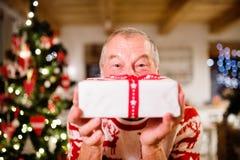 Ανώτερο άτομο μπροστά από το χριστουγεννιάτικο δέντρο που κρατά ένα δώρο Στοκ Εικόνες