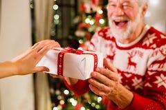Ανώτερο άτομο μπροστά από το χριστουγεννιάτικο δέντρο που κρατά ένα δώρο Στοκ εικόνα με δικαίωμα ελεύθερης χρήσης