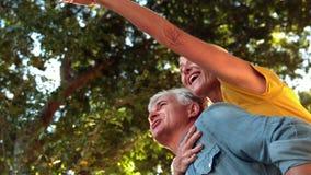 Ανώτερο άτομο που δίνει στο συνεργάτη του ένα σηκώνω στην πλάτη την ηλιόλουστη ημέρα φιλμ μικρού μήκους
