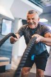 Ανώτερο άτομο που ασκεί με τα σχοινιά στη γυμναστική στοκ εικόνα με δικαίωμα ελεύθερης χρήσης