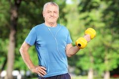 Ανώτερο άτομο που ασκεί με το βάρος στο πάρκο στοκ εικόνα