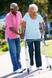Ανώτερο άτομο που βοηθά τη σύζυγο με το πλαίσιο περπατήματος Στοκ φωτογραφία με δικαίωμα ελεύθερης χρήσης
