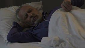 Ανώτερο άτομο που βρίσκεται στο κρεβάτι και που κοιμάται στο σκοτεινό δωμάτιο, που αποκαθιστά την ενέργεια τη νύχτα απόθεμα βίντεο