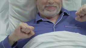 Ανώτερο άτομο που βρίσκεται στο κρεβάτι, που τεντώνει μετά από να ξυπνήσει, χαμόγελο στο πρόσωπο, υγιής ύπνος απόθεμα βίντεο