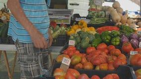 Ανώτερο άτομο που επιλέγει τα λαχανικά στην αγροτική αγορά φρούτων και λαχανικών απόθεμα βίντεο