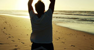 Ανώτερο άτομο που κάνει την τεντώνοντας άσκηση στην παραλία απόθεμα βίντεο