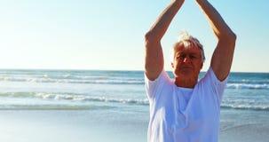 Ανώτερο άτομο που κάνει τη γιόγκα στην παραλία απόθεμα βίντεο