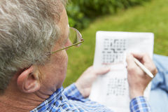 Ανώτερο άτομο που κάνει το γρίφο σταυρόλεξων στον κήπο Στοκ φωτογραφίες με δικαίωμα ελεύθερης χρήσης