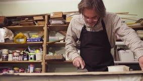 Ανώτερο άτομο που καλύπτει μια ξύλινη επιφάνεια με το τσιμέντο φιλμ μικρού μήκους
