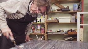 Ανώτερο άτομο που καλύπτει τη χρωματισμένη ξύλινη επιφάνεια με ένα βερνίκι απόθεμα βίντεο