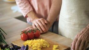 Ανώτερο άτομο που κόβει το κίτρινο πιπέρι και που κρατά τα χέρια συζύγων, οικιακές μικροδουλειές, φλερτ απόθεμα βίντεο