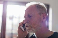 Ανώτερο άτομο που μιλά στο τηλέφωνο, το σκληρές φως και την επίδραση φλογών Στοκ φωτογραφία με δικαίωμα ελεύθερης χρήσης