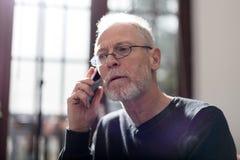 Ανώτερο άτομο που μιλά στο τηλέφωνο, το σκληρές φως και την επίδραση φλογών Στοκ Εικόνες