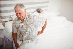 Ανώτερο άτομο που πάσχει από τον πόνο στην πλάτη που κάθεται στο κρεβάτι Στοκ Εικόνες