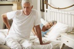 Ανώτερο άτομο που πάσχει από τον πόνο στην πλάτη που ξεπερνά το κρεβάτι Στοκ εικόνα με δικαίωμα ελεύθερης χρήσης