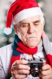 Ανώτερο άτομο που παίρνει τη φωτογραφία στο υπόβαθρο Χριστουγέννων Στοκ εικόνα με δικαίωμα ελεύθερης χρήσης