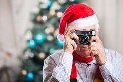Ανώτερο άτομο που παίρνει τη φωτογραφία στο υπόβαθρο Χριστουγέννων Στοκ Εικόνα