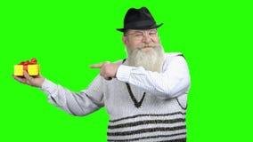 Ανώτερο άτομο που παρουσιάζει κιβώτιο δώρων στην πράσινη οθόνη απόθεμα βίντεο
