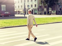 Ανώτερο άτομο που περπατά κατά μήκος της διάβασης πεζών πόλεων στοκ εικόνες