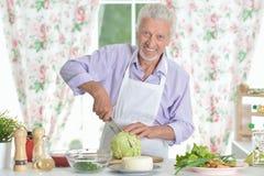 Ανώτερο άτομο που προετοιμάζει το γεύμα στην κουζίνα Στοκ Εικόνες