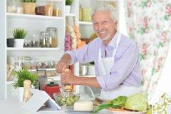 Ανώτερο άτομο που προετοιμάζει το γεύμα στην κουζίνα Στοκ εικόνες με δικαίωμα ελεύθερης χρήσης