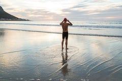 Ανώτερο άτομο που προετοιμάζεται να κολυμπήσει στη θάλασσα στην αυγή στοκ εικόνα με δικαίωμα ελεύθερης χρήσης