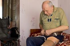 Ανώτερο άτομο που συνδέει το τεχνητό πόδι του στο σπίτι στοκ φωτογραφία με δικαίωμα ελεύθερης χρήσης
