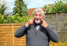 Ανώτερο άτομο που τραβά το στόμα σε ένα χαμόγελο στοκ φωτογραφίες με δικαίωμα ελεύθερης χρήσης