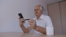 Ανώτερο άτομο που ψωνίζει on-line με την πιστωτική κάρτα που χρησιμοποιεί το smartphone στο σπίτι Σε απευθείας σύνδεση τραπεζικές φιλμ μικρού μήκους
