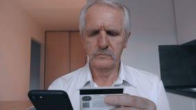 Ανώτερο άτομο που ψωνίζει on-line με την πιστωτική κάρτα που χρησιμοποιεί το smartphone στο σπίτι στην κουζίνα Σε απευθείας σύνδε απόθεμα βίντεο