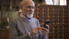 Ανώτερο άτομο στα στρογγυλά γυαλιά που χρησιμοποιούν το smartphone του απόθεμα βίντεο