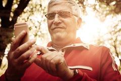 Ανώτερο άτομο στην αθλητική ενδυμασία που στέκεται στο πάρκο μια δακτυλογράφηση ο στοκ εικόνα
