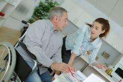 Ανώτερο άτομο στην αναπηρική καρέκλα με τον εκτεταμένο βοηθό προσοχής στοκ εικόνα με δικαίωμα ελεύθερης χρήσης