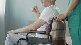 Ανώτερο άτομο στην αναπηρική καρέκλα, νοσοκόμα που φροντίζει το με ειδικές ανάγκες υπομονετικό, ιατρικό κέντρο απόθεμα βίντεο