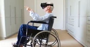 Ανώτερο άτομο στην αναπηρική καρέκλα που χρησιμοποιεί vr την κάσκα στην κρεβατοκάμαρα απόθεμα βίντεο
