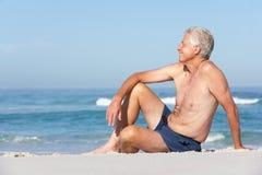 Ανώτερο άτομο στη συνεδρίαση διακοπών στην αμμώδη παραλία Στοκ Φωτογραφία