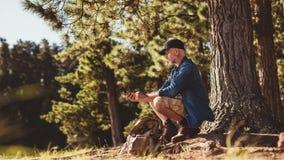 Ανώτερο άτομο στο πεζοπορώ στη φύση που χρησιμοποιεί μια πυξίδα Στοκ φωτογραφία με δικαίωμα ελεύθερης χρήσης