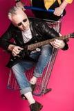 Ανώτερο άτομο στο σακάκι δέρματος και γυαλιά ηλίου που κάθονται στο καροτσάκι αγορών και την ηλεκτρική κιθάρα παιχνιδιού Στοκ Εικόνες
