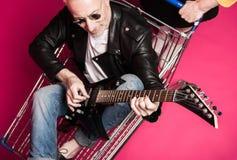 Ανώτερο άτομο στο σακάκι δέρματος και γυαλιά ηλίου που κάθονται στο καροτσάκι αγορών και την ηλεκτρική κιθάρα παιχνιδιού Στοκ φωτογραφία με δικαίωμα ελεύθερης χρήσης
