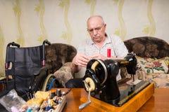 Ανώτερο άτομο στο σπίτι με την εκλεκτής ποιότητας ράβοντας μηχανή Στοκ Φωτογραφία