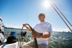Ανώτερο άτομο στο τιμόνι στη βάρκα ή γιοτ που πλέει στη θάλασσα Στοκ φωτογραφία με δικαίωμα ελεύθερης χρήσης
