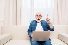 Ανώτερο άτομο χρησιμοποιώντας το lap-top και δείχνοντας επάνω με το δάχτυλο Στοκ φωτογραφία με δικαίωμα ελεύθερης χρήσης